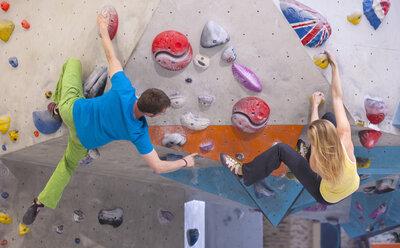 Germany, Bavaria, Munich, Young man helping woman to climb - HSIYF000187