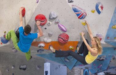 Germany, Bavaria, Munich, Young man helping woman to climb - HSIYF000216