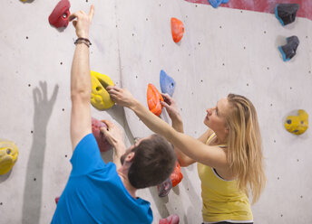 Germany, Bavaria, Munich, Young man helping woman to climb - HSIYF000189