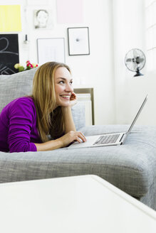 Germany, Bavaria, Munich, Young woman using laptop, smiling - SPOF000337