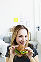 Germany, Bavaria, Munich, Portrait of young woman holding sandwich, smiling - SPOF000307