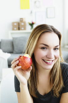 Germany, Bavaria, Munich, Portrait of young woman holding apple, smiling - SPOF000309