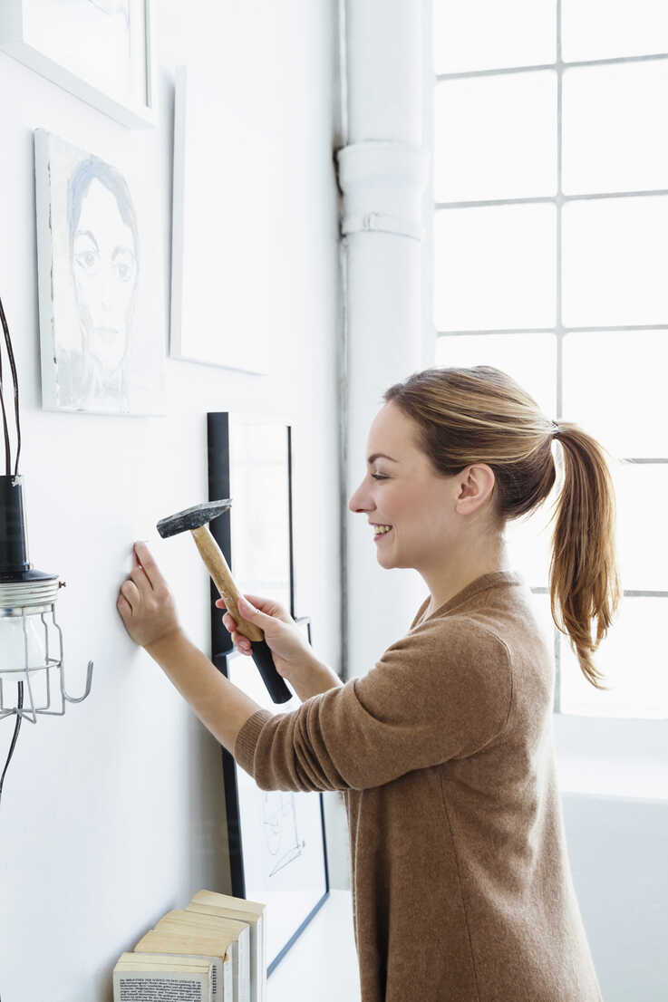 Germany, Bavaria, Munich, Young woman hammering wall, smiling - SPOF000341 - 4r3p/Westend61