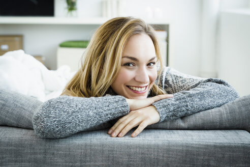 Germany, Bavaria, Munich, Portrait of young woman relaxing on couch, smiling - SPOF000324