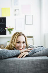 Germany, Bavaria, Munich, Portrait of young woman relaxing on couch, smiling - SPOF000325