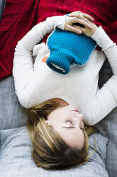 Germany, Bavaria, Munich, Young woman sleeping on couch with hot water bottle - SPOF000326