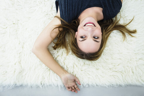 Germany, Bavaria, Munich, Young woman lying on carpet, smiling - SPOF000272