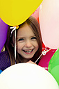 Portrait of girl in middle of balloons, smiling - SARF000008
