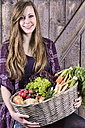 Germany, Portrait of teenage girl holding basket with organic vegetables, smiling - ONF000157