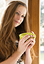 Germany, Portrait of teenage girl drinking coffee, smiling - ONF000173