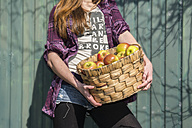 Germany, Teenage girl holding basket with organic apples - ONF000159