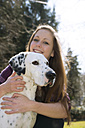 Germany, Portrait of teenage girl with dalmatian dog, smiling - ONF000165