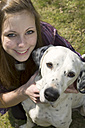 Germany, Portrait of teenage girl with dalmatian dog, smiling - ONF000167