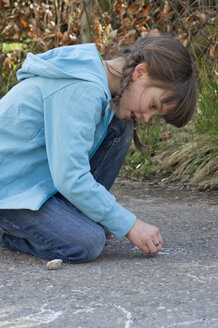 Germany, Tuebingen, Girl drawing hopscotch on street with chalk - LV000030