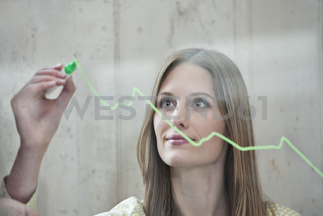 Germany, North Rhine Westphalia, Cologne, Businesswoman drawing graph on glass, looking away - FMKF000767