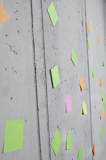 Germany, North Rhine Westphalia, Cologne, Adhesive notes stuck on wall, close up - FMKF000725
