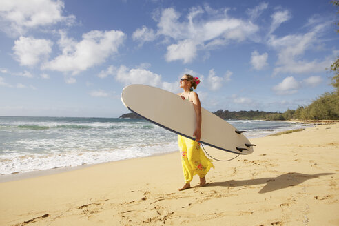 USA, Hawaii, Woman standing with surfboard  on beach - SKF001278