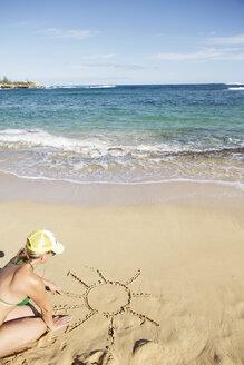 USA, Hawaii, Mid adult woman drawing sun on sand - SKF001294
