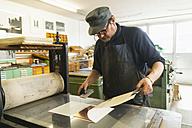 Germany, Bavaria, Mature man looking at deckle edge paper in print shop - TC003436