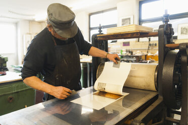 Germany, Bavaria, Mature man looking at deckle edge paper in print shop - TC003439