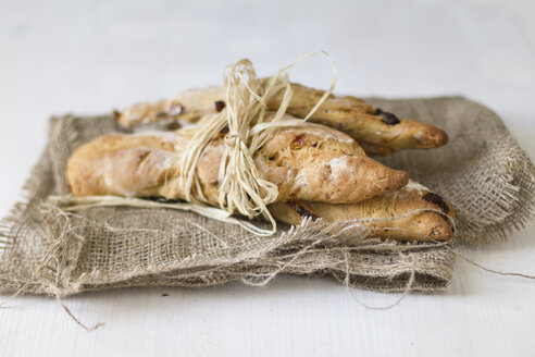 Breadsticks tied up with straw on jute sack, close up - SBDF000022