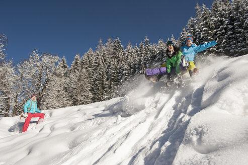 Austria, Salzburg, Young man and women with sledge in snow at Altenmarkt Zauchensee - HHF004585