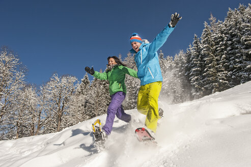 Austria, Salzburg, Young woman and man snowshoeing at Altenmarkt Zauchensee - HHF004582