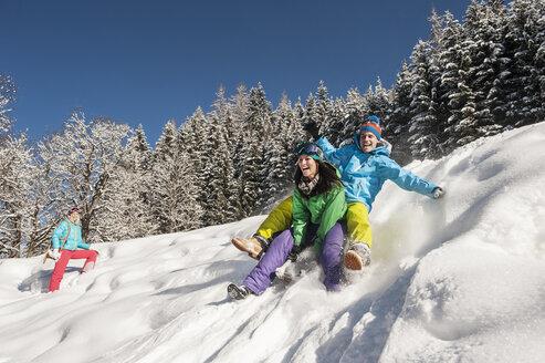 Austria, Salzburg, Young man and women with sledge in snow at Altenmarkt Zauchensee - HHF004581