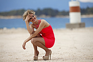 Greece, Young woman crouching on sand at sea, smiling - AJF000007