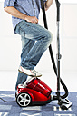 Mature man standing with vaccuum cleaner - MAEF006524