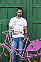 Germany, Bavaria, Portrait of mature man with pink bicycle - MAEF006533