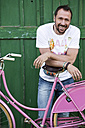 Germany, Bavaria, Portrait of mature man leaning on pink bicycle, smiling - MAEF006531