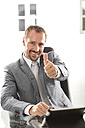 Germany, Portrait of businessman showing thumbs up, smiling - MAEF006632