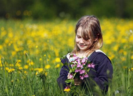 Germany, Baden Wuerttemberg, Girl sitting in meadow - SLF000089