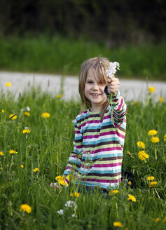 Germany, Baden Wuerttemberg, Girl sitting in meadow - SLF000090