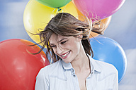 Germany, Cologne, Young woman with balloons, close up - FMKF000827