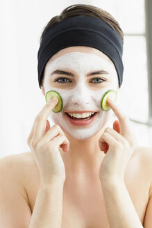 Germany, Bavaria, Munich, Portrait of young woman with cucumber mask, close up - SPOF000416