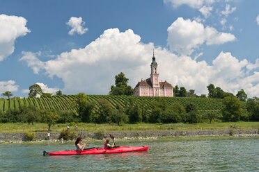 Germany, Mother and daughter rowing boat in Lake Constance and Baroque Church in background - SH000696