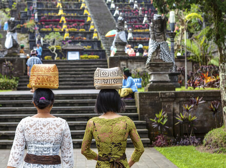 Indonesia, Women carrying basket on head and walking at Pura Penataran Agung temple - AM000054