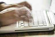 Germany, North Rhine Westphalia, Cologne, Young man typing on laptop, close up - JAT000003