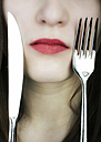 Teenage girl with knife and fork on face, close up - JAT000010