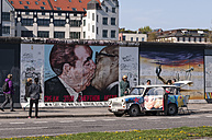 Germany, Berlin, Trabant in front of mural painting of brotherly kiss between Leonid Brezhnev and Erich Honecker - CB000060