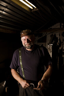 Portrait of smiling blacksmith in his workshop - CNF000056