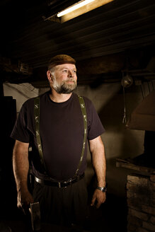 Portrait of confident blacksmith in his workshop - CNF000067