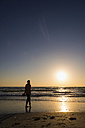 USA, Florida, Indian Rocks Beach, Mature woman walking on beach during sunset - ABAF000840