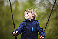 Germany, Baden Wuerttemberg, Girl swinging on swing - SLF000128