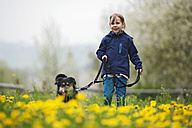 Germany, Baden Wuerttemberg, Portrait of girl walking with dog in meadow - SLF000126