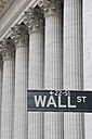 USA, New York State, Manhattan, Wall street sign against Stock Exchange pillars - RUEF001034