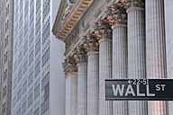 USA, New York State, Manhattan, Wall street sign against Stock Exchange pillars - RUE001036