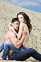 Germany, Bavaria, Young topless lovers in sand dunes - MAEF006725